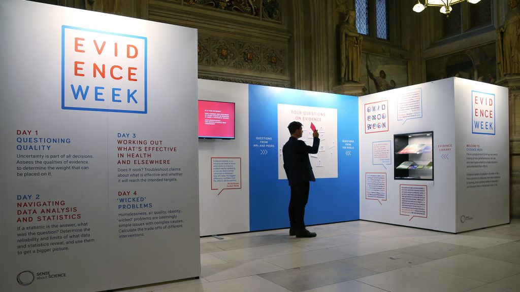 A person standing in front of the Evidence Week exhibition stand holding a red viewing glass in the UK Parliament.
