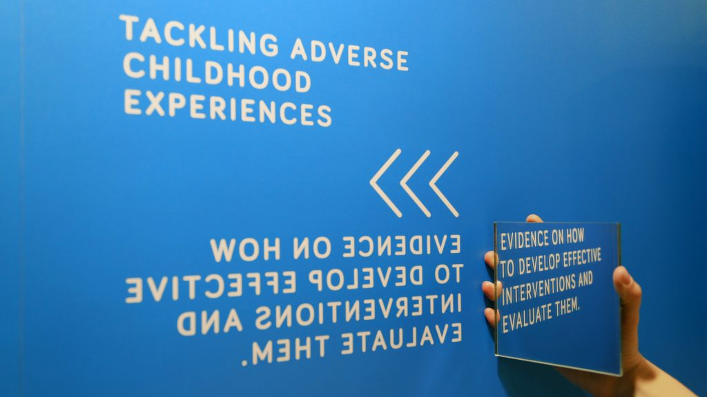 A hand holding a square shaped mirror agains the blue exhibition stand to reveal a white text message that has been printed in reversed direction.