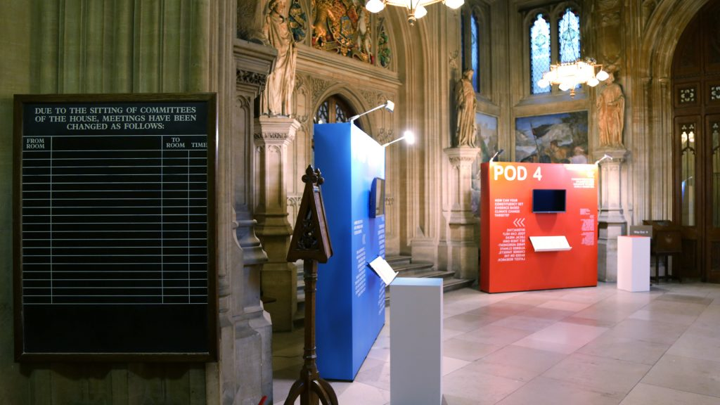 Photograph showing half of the Upper Waiting Hall of the UK Parliament with two exhibition stands and two pillars.