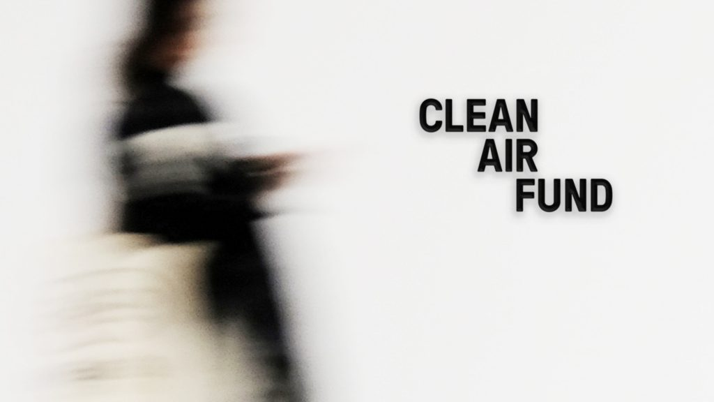 The Clean Air Fund logo as it would appear on a wall, with a person walking past.