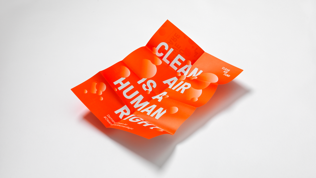 "A folded poster reading ""CLEAN AIR IS A HUMAN RIGHT"" in bold, white text on an orange background."