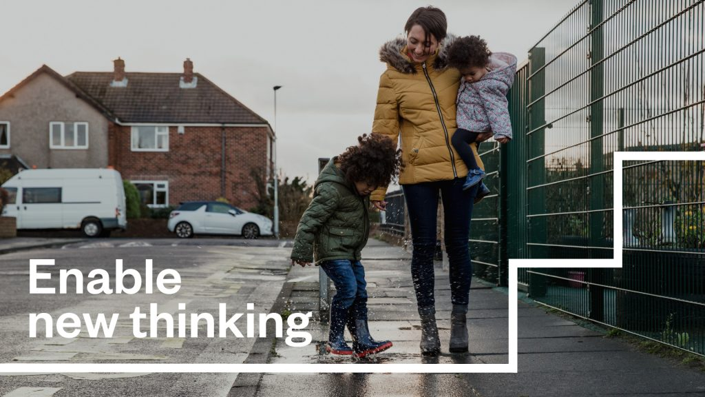 "An image of a parent and two children, with the text ""Enable new thinking""."