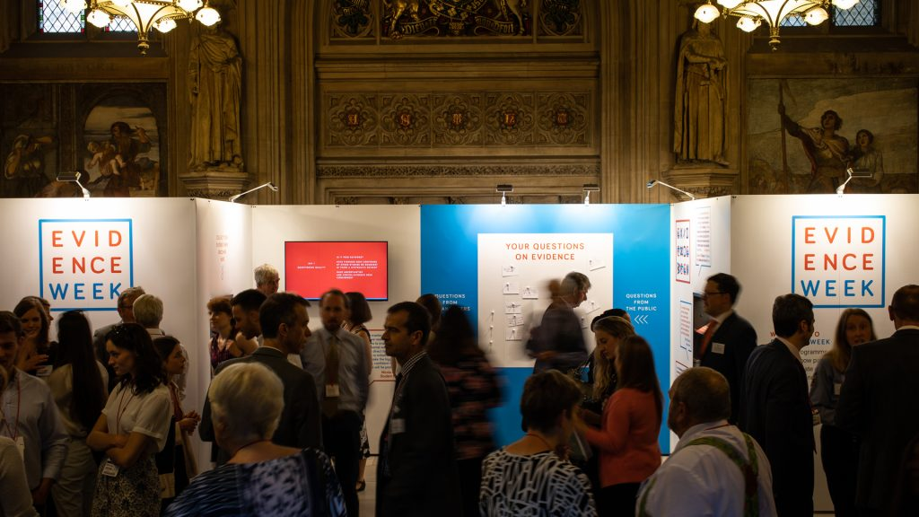 A crowd of people in front of the exhibition stand in the Upper Waiting Hall of the UK Parliament.