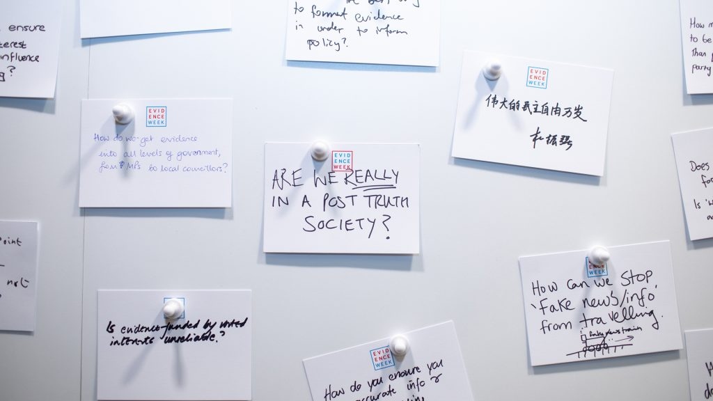 A white pin wall with attached hand written notes on the Evidence Week exhibition stand.