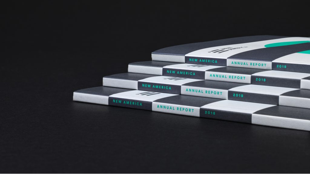 The spines of four stacked annual reports.