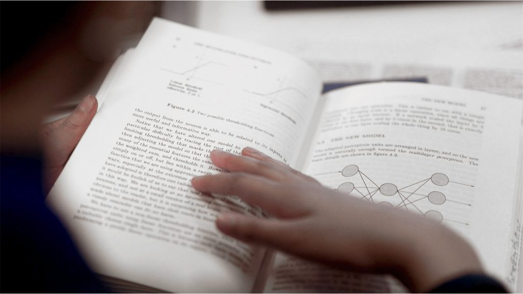 Photograph of a young person reading a physics book.