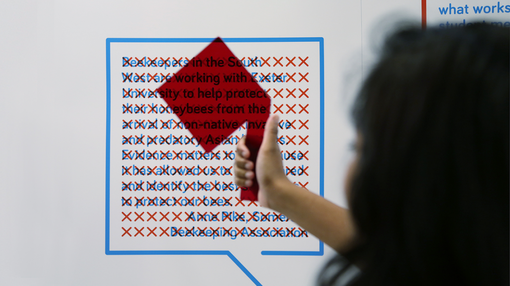 A person holds a red viewing glass up to the Evidence Week exhibition stand, revealing hidden text.