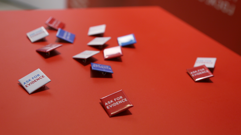 "Pins from the Evidence Week event, reading ""ASK FOR EVIDENCE"" in white, red and blue versions."